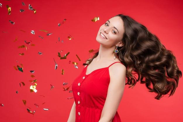 Porträt der entzückenden lächelnden jungen frau mit dem langen gelockten haar, das am roten studiohintergrund aufwirft Premium Fotos