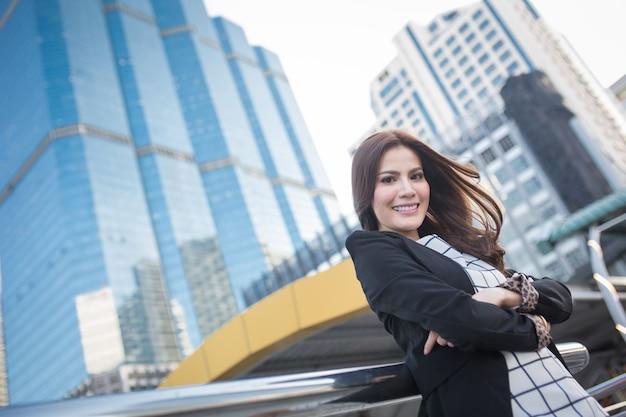 Porträt der erfolgreichen intelligenten geschäftsfrau, die überzeugt und das lächeln schaut Premium Fotos