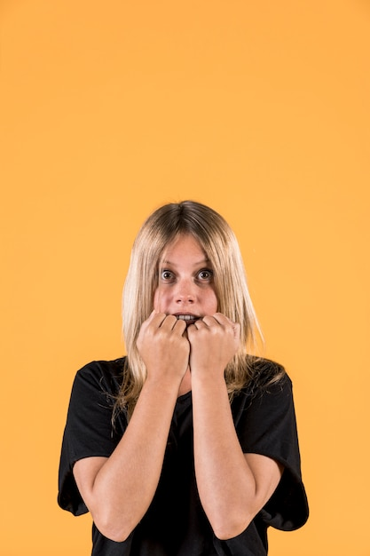Porträt der erschrockenen frau stehend gegen gelben hintergrund Kostenlose Fotos