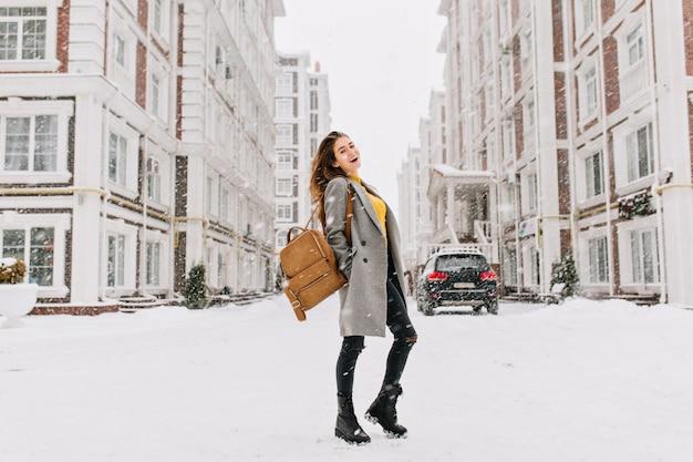 Porträt der europäischen frau in voller länge trägt eleganten mantel bei schneebedecktem wetter. fröhliche junge frau mit stilvollem rucksack, der auf hauptstadtstraße im wintertag steht. Kostenlose Fotos