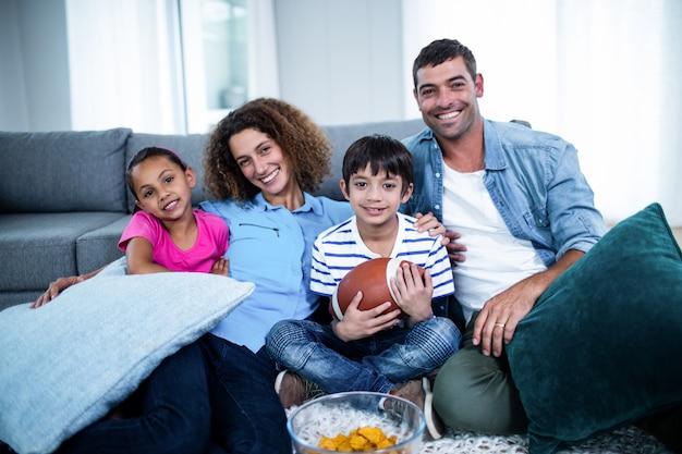 Porträt der familie amerikanisches fußballspiel im fernsehen aufpassend Premium Fotos