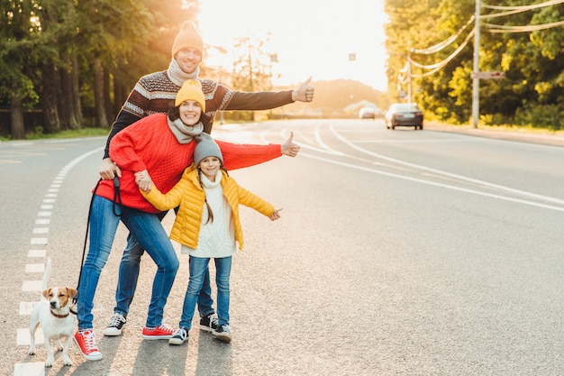 Porträt der familie: mutter, vater und kleine tochter gehen mit haustier, stehen auf straße Premium Fotos