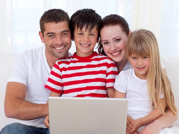 Porträt der familie zu hause unter verwendung eines laptops Premium Fotos