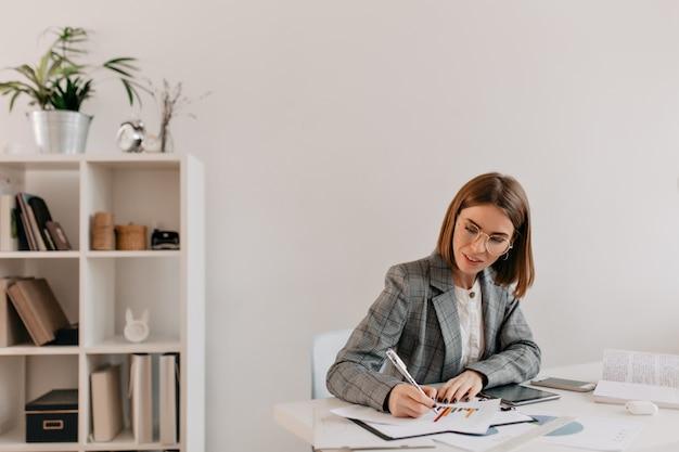Porträt der frau, das diagramm mit erklärungen ergänzt. geschäftsdame im hellen outfit, das im weißen büro arbeitet. Kostenlose Fotos