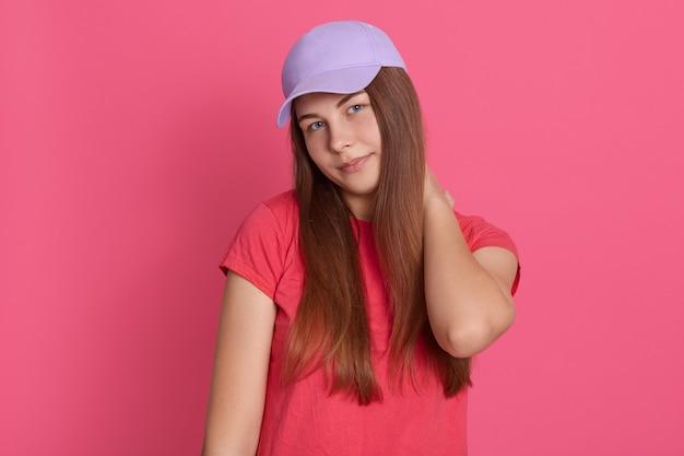 Porträt der frau, die ihren hals im unbehagen gegen rosa hintergrund hält, frau mit nackenschmerzen Kostenlose Fotos