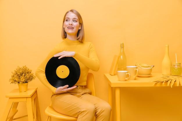 Porträt der frau ein vinyl in einer gelben szene halten Kostenlose Fotos
