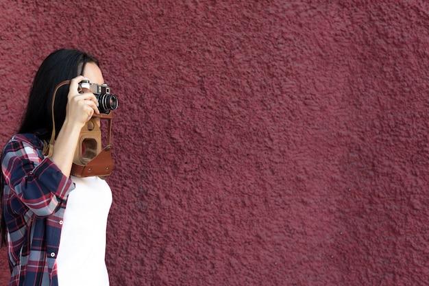 Porträt der frau foto mit kamera gegen kastanienbraune strukturierte wand machend Kostenlose Fotos
