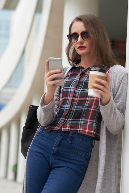 Porträt der frau in der freizeitkleidung unter verwendung des smartphone beim kaffee draußen trinken Kostenlose Fotos