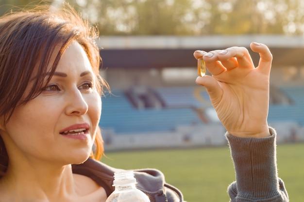 Porträt der frau kapsel des vitamins e nehmend Premium Fotos