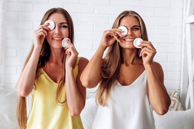 Porträt der frau lächelnd und baumwollauflage gegen weißen hintergrund verwendend Premium Fotos