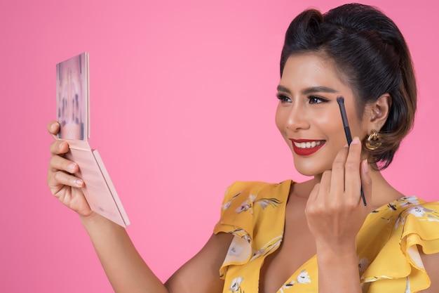 Porträt der frau mit make-upbürste und kosmetik Kostenlose Fotos