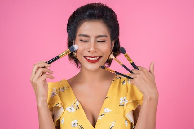Porträt der frau mit make-upbürsten-berufsshow Kostenlose Fotos