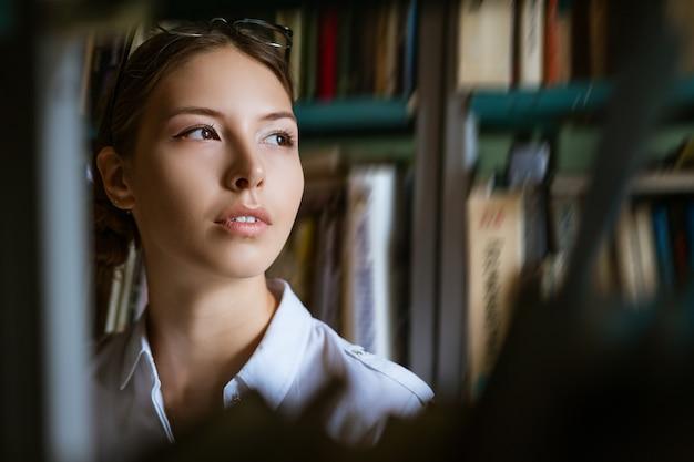 Porträt der frau vor dem hintergrund der bücher in der bibliothek, blick durch die regale der bücher. das konzept der vorbereitung auf die prüfungen Premium Fotos