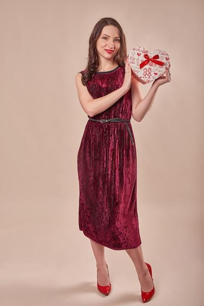 Porträt der fröhlichen frau im roten kleid, das geschenkbox hält Premium Fotos