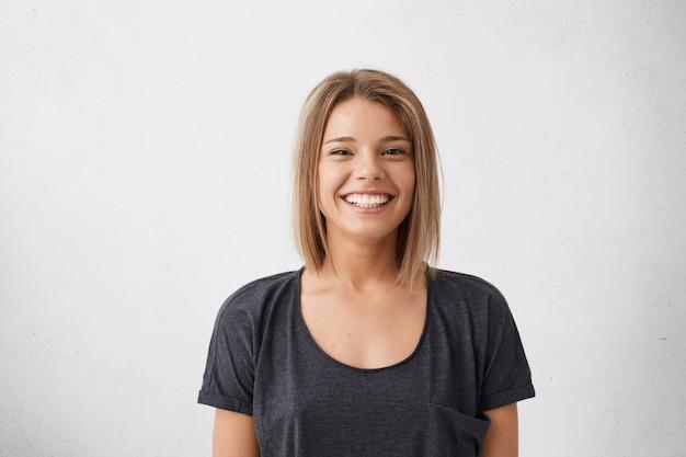 Porträt der fröhlichen schönen frau mit der trendigen frisur, die dunkle charmante augen und ein ansprechendes lächeln hat. menschen, glück, emotionen und lifestyle-konzept Kostenlose Fotos