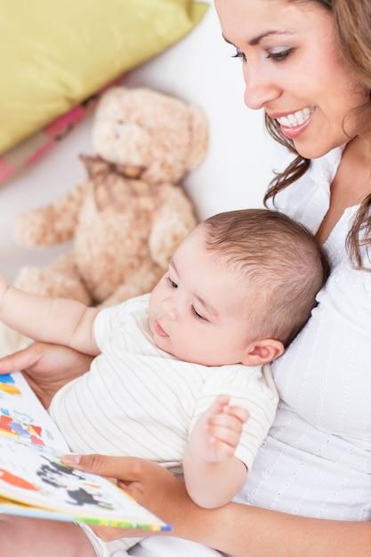 Porträt der frohen mutter ein buch zu ihrem baby lesend, das im wohnzimmer sitzt Premium Fotos