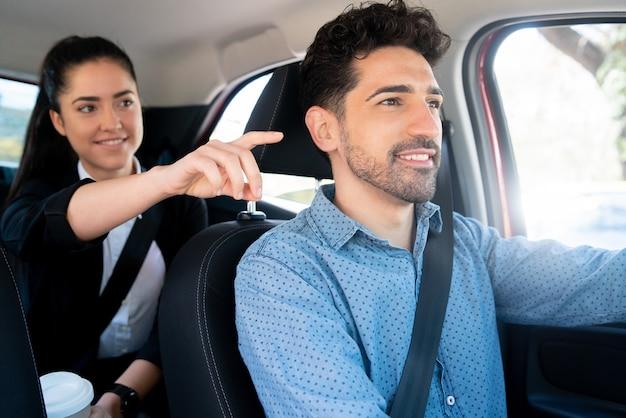 Porträt der geschäftsfrau, die etwas zu ihrem taxifahrer zeigt Premium Fotos