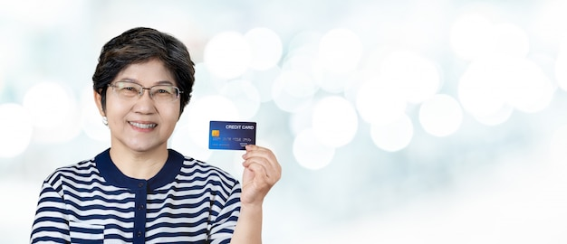 Porträt der glücklichen älteren asiatischen frauengriffkreditkarte Premium Fotos