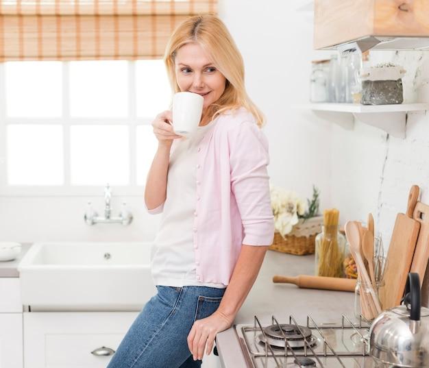 Porträt der glücklichen älteren frau, die kaffee trinkt Kostenlose Fotos
