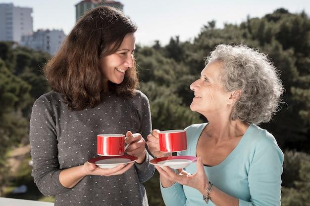 Porträt der glücklichen älteren mutter und ihres trinkenden tees der tochter Kostenlose Fotos