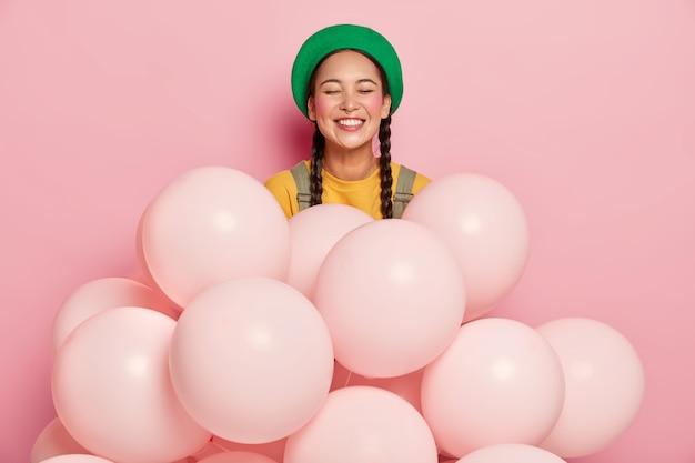 Porträt der glücklichen asiatischen dame im grünen hut, hat zwei zöpfe, rote wangen, drückt positive gefühle aus, steht in der nähe vieler einfarbiger luftballons Kostenlose Fotos