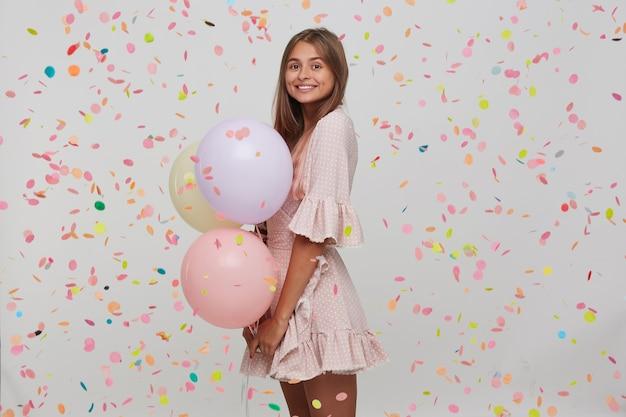 Porträt der glücklichen attraktiven jungen frau mit dem langen gefärbten pastellrosa haar trägt tupfenrosa kleid, das bunte luftballons in der hand hält und partei über weißer wand mit isoliert hat Kostenlose Fotos