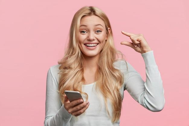 Porträt der glücklichen entzückten jungen niedlichen frau zeigt geldbetrag, den sie diesen monat erhalten hat, hält modernes handy in händen, liest nachricht, isoliert über rosa wand. das ist zu klein Kostenlose Fotos