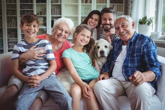 Porträt der glücklichen familie, die auf sofa im wohnzimmer sitzt Premium Fotos