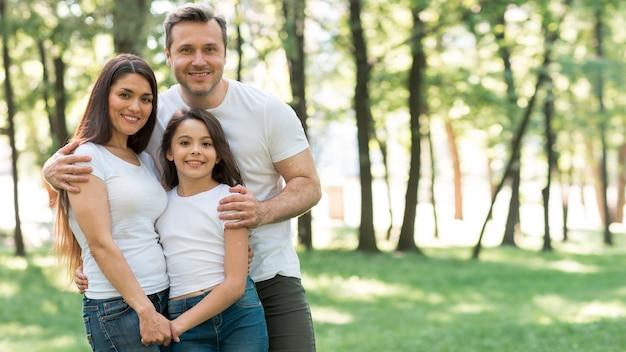 Porträt der glücklichen familie im weißen t-shirt, das zusammen am park steht Kostenlose Fotos