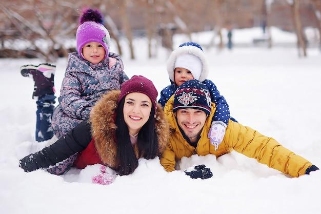 Porträt der glücklichen familie im winter. lächelnde eltern mit ihren kindern. hübscher vater und schöne mutter mit kleinen süßen töchtern, die spaß im showpark haben. hübsche kinder, nette frau Premium Fotos