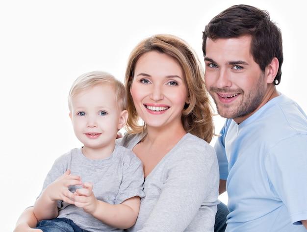 Porträt der glücklichen familie mit dem kleinen kind, das kamera betrachtet - lokalisiert Kostenlose Fotos