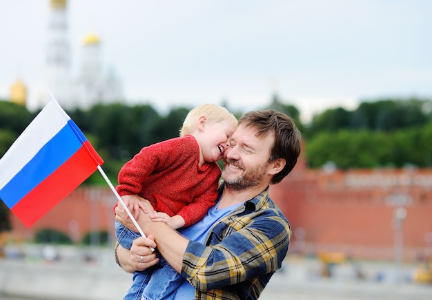 Porträt der glücklichen familie mit russischer flagge mit moskau der kreml Premium Fotos