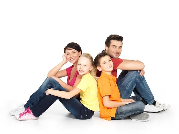 Porträt der glücklichen familie mit zwei kindern, die im studio auf weißem boden sitzen Kostenlose Fotos