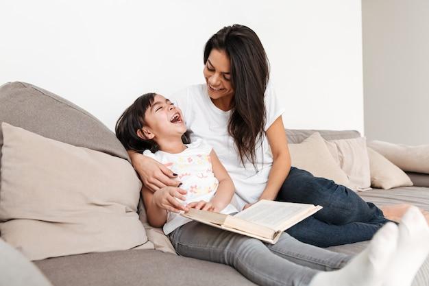 Porträt der glücklichen frau mit ihrer kleinen tochter, die lächelt, während sie im wohnzimmer ruht, und buch liest Premium Fotos