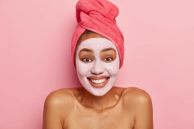 Porträt der glücklichen frau trägt ton pflegende gesichtsmaske auf, hat fröhlichen ausdruck, ist gut gelaunt, genießt verjüngungsbehandlung, trägt rosiges handtuch auf nassem haar Kostenlose Fotos