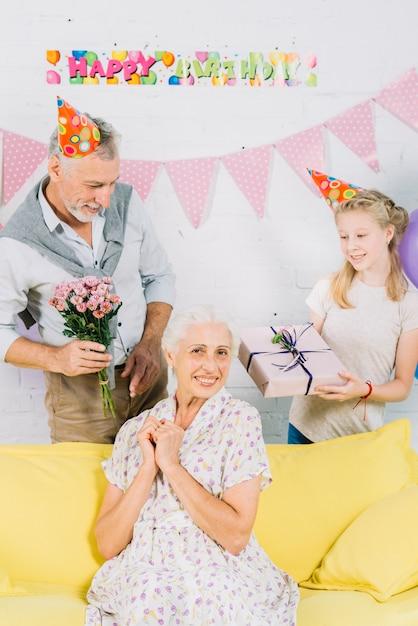 Porträt der glücklichen frau vor ehemann und enkelin mit geburtstagsgeschenken Kostenlose Fotos
