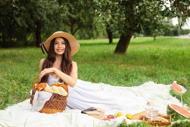 Porträt der glücklichen hübschen jungen dame im hut, die ruhe auf picknick im park hat, während sie einen korb brot in den händen hält Premium Fotos