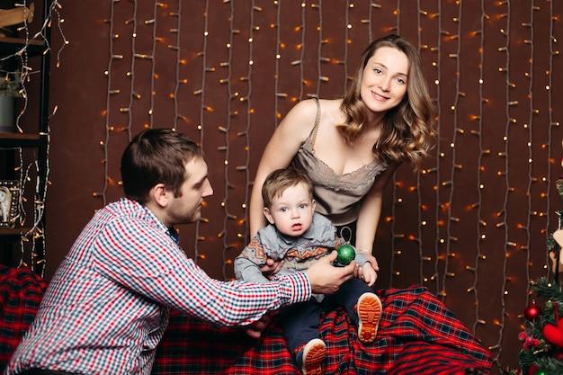 Porträt der glücklichen jungen familie, die zusammen auf bank während weihnachten im studio sitzt, posiert, lächelt und nach vorne schaut Kostenlose Fotos
