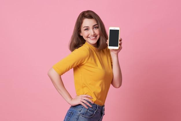 Porträt der glücklichen jungen frau, die am handy des leeren bildschirms lokalisiert über rosa darstellt. Premium Fotos