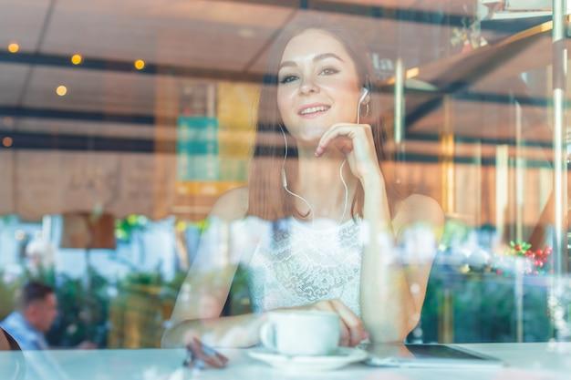 Porträt der glücklichen jungen geschäftsfrau mit becher in den händen kaffee am restaurant trinkend Premium Fotos