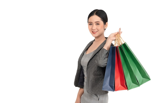 Porträt der glücklichen lächelnden asiatischen frau halten einkaufstasche auf weißem hintergrund. Premium Fotos