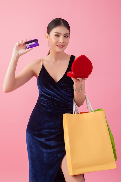 Porträt der glücklichen lächelnden frauengriffeinkaufstasche Kostenlose Fotos