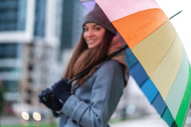 Porträt der glücklichen lächelnden freudigen frau in der warmen kleidung mit hellem mehrfarbigem regenbogenschirm Premium Fotos