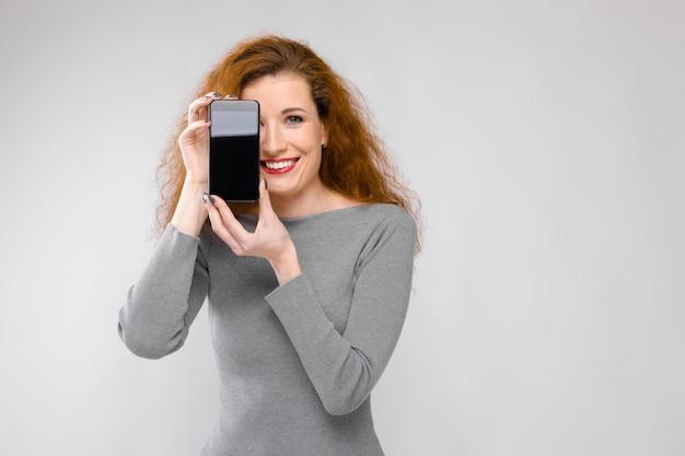 Porträt der glücklichen lächelnden jungen frau der schönen rothaarigen in der grauen kleidung, die handy zeigt Premium Fotos