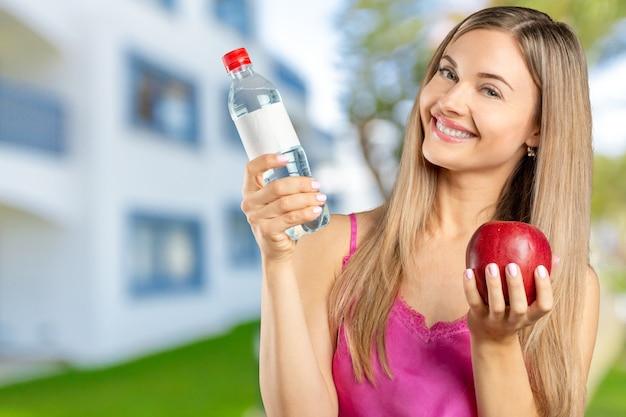 Porträt der glücklichen lächelnden jungen schönheit, die roten apfel isst Premium Fotos