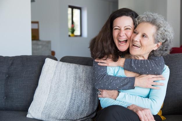Porträt der glücklichen mittleren erwachsenen frau, die ihre ältere mutter umfasst Kostenlose Fotos