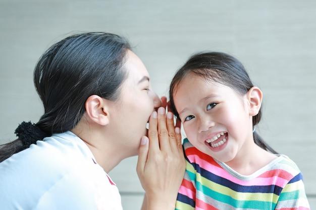 Porträt der glücklichen mutter ein geheimnis etwas zu ihrem kleinen tochterohr flüsternd. Premium Fotos
