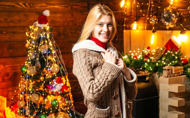 Porträt der glücklichen positiven frau, die am hölzernen hintergrund im dekorierten raum steht. familienurlaub Premium Fotos
