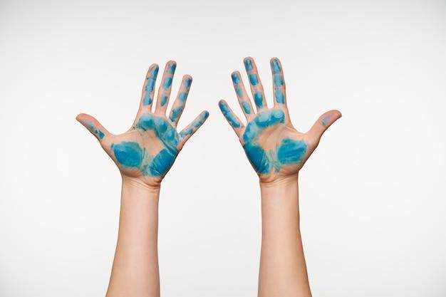 Porträt der hellhäutigen frauenhände mit blauer farbe, die handflächen zeigt und alle finger getrennt hält, isoliert auf weiß Kostenlose Fotos