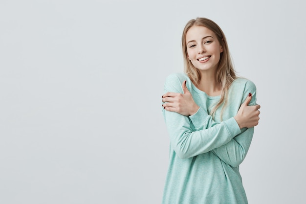 Porträt der herrlichen positiven jungen kaukasischen frau mit charmantem lächeln und langen blonden haaren, die weichen stoff ihres neuen hellblauen oberteils genießen, das gegen graue wand aufwirft Kostenlose Fotos